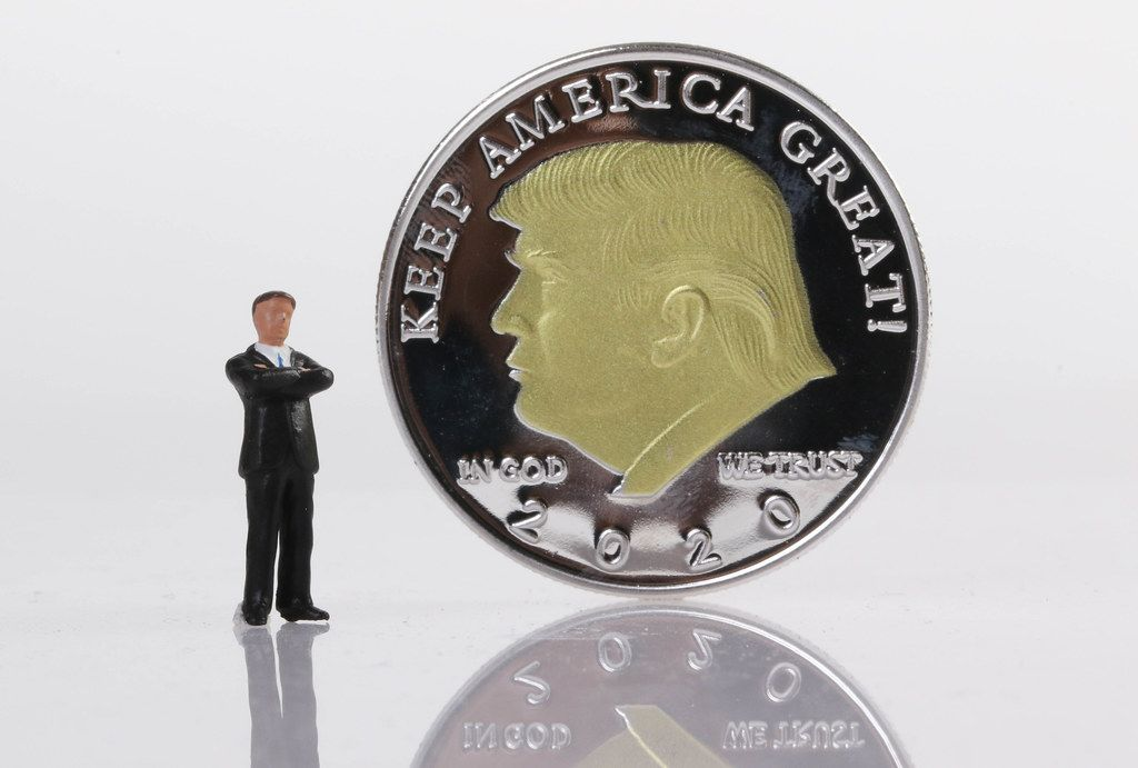 Businessman standing next to a Silver coin with Donald Trump on it