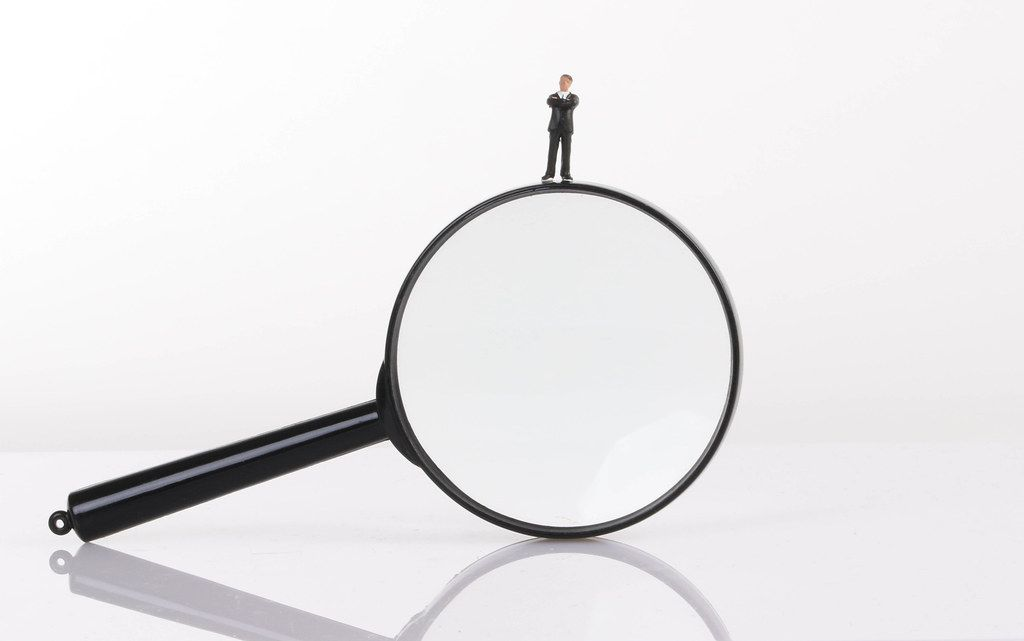 Businessman standing on magnifying glass