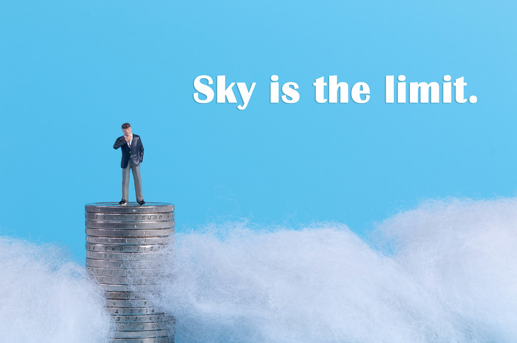 Businessman standing on top of a coinstack surrounded with clouds and Sky is the limit text