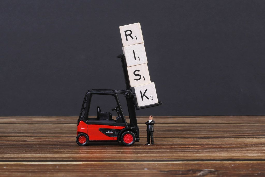 Businessman standing under wooden blocks with risk text