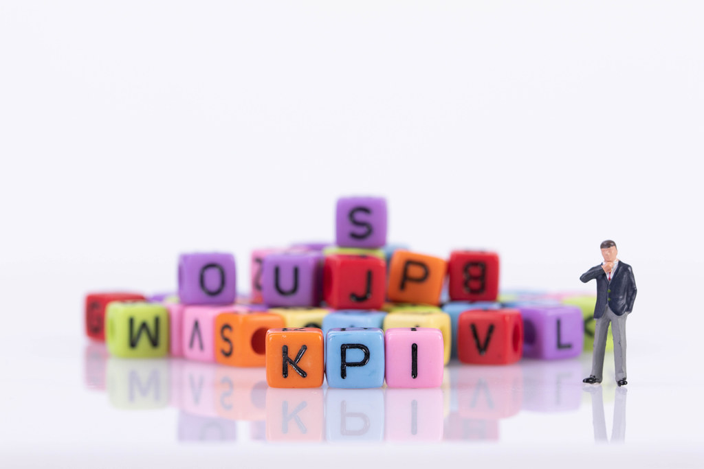 Businessman with colorful toy blocks with KPI text