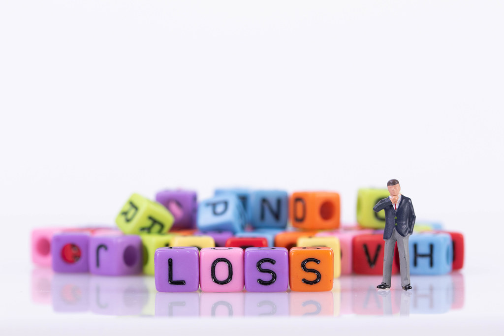 Businessman with colorful toy blocks with Loss text