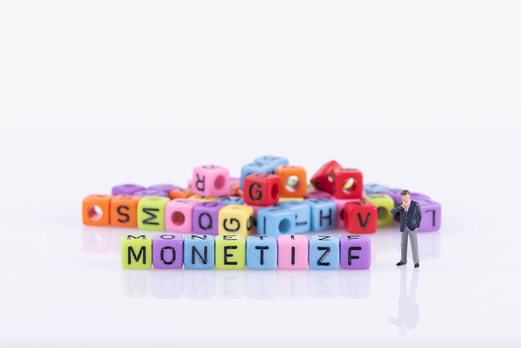 Businessman with colorful toy blocks with Monetize text