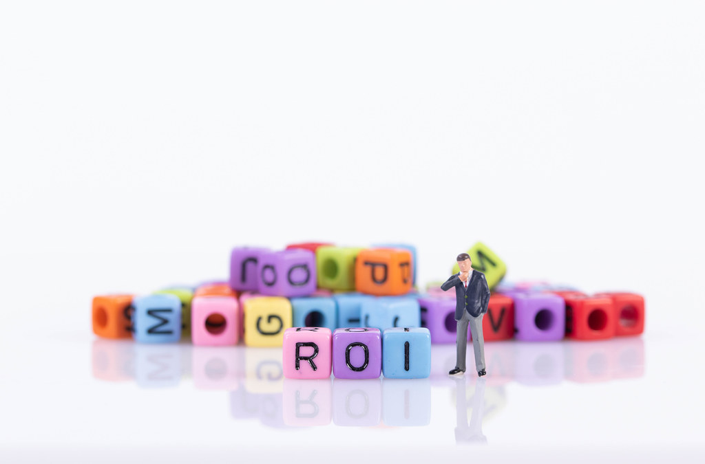 Businessman with colorful toy blocks with ROI text