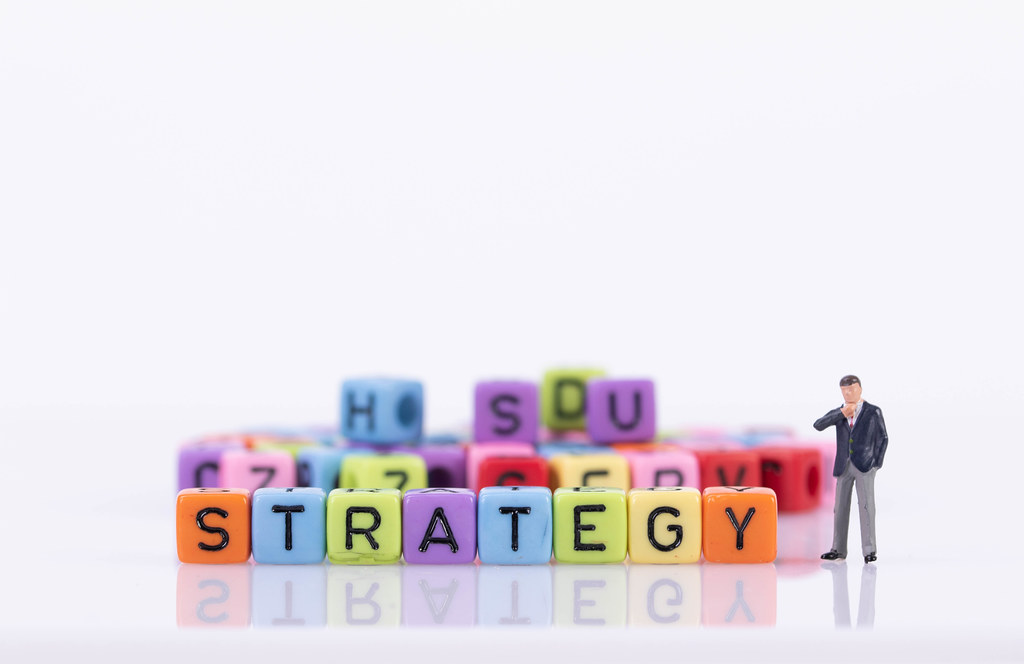 Businessman with colorful toy blocks with Strategy text