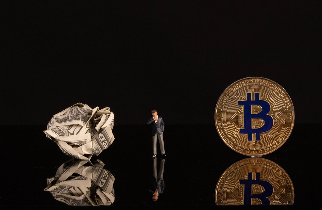 Businessman with crumpled money and golden Bitcoin