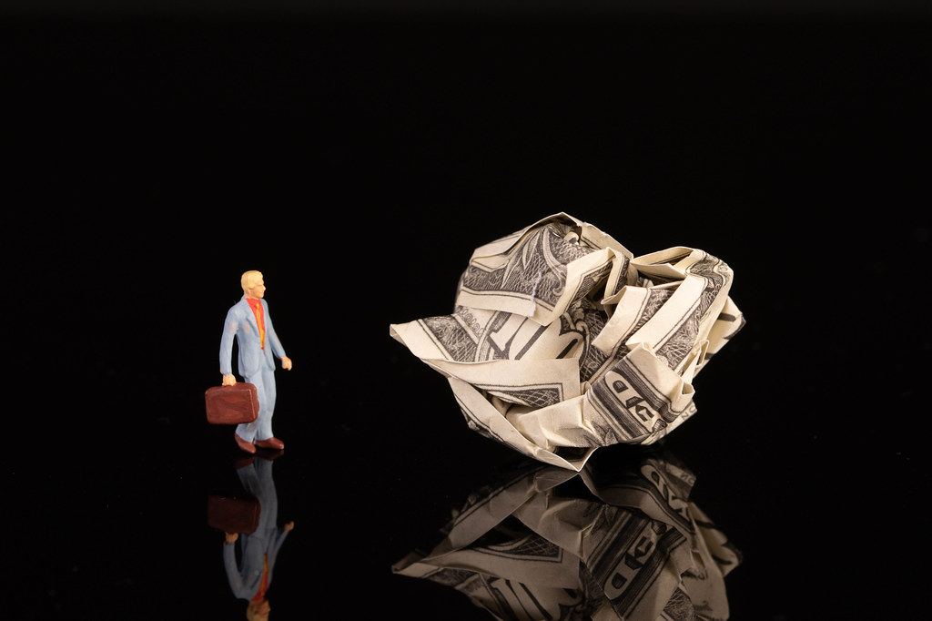 Businessman with crumpled money on black background