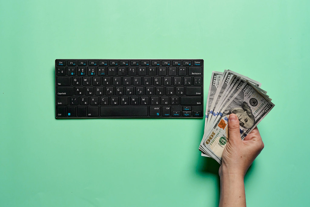 Businesswoman holding cash and using computer for e-commerce