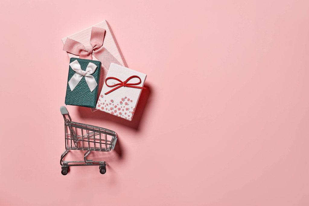 Buying gifts concept - present boxes in the shopping cart