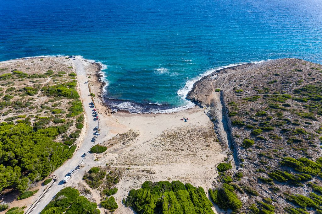 Cala Mitjana near Artà, Mallorca. Aerial view of sandy beach with very few people and cars