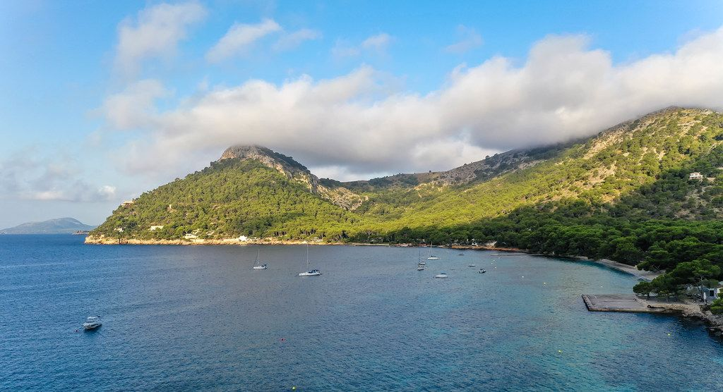 Cala Pi de la Posada on the Formentor peninsula on Mallorca. Bay with boats and hills covered with trees