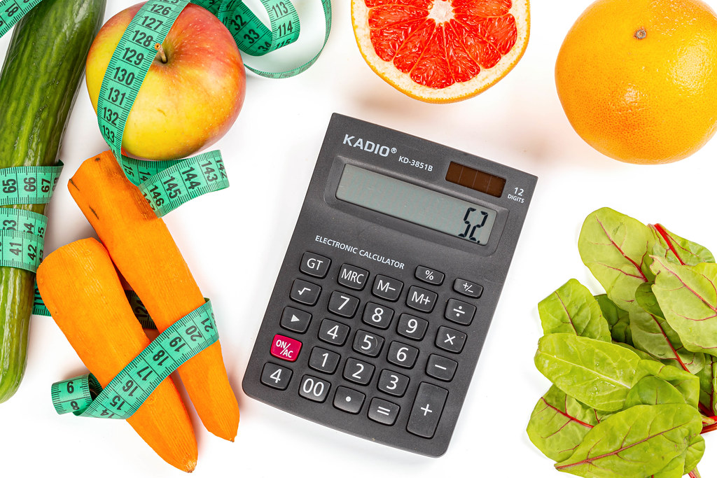 Calculator on white background with fresh vegetables, fruits and measuring tape, top view