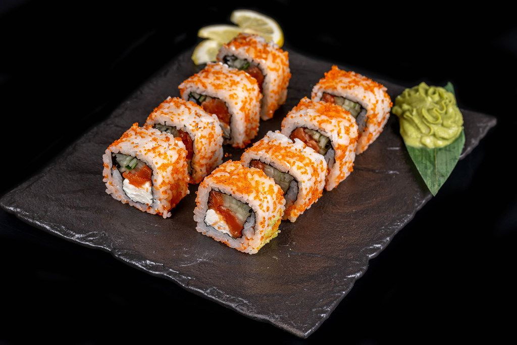 California set rolls with salmon, wasabi sauce and lemon slices on a dark background