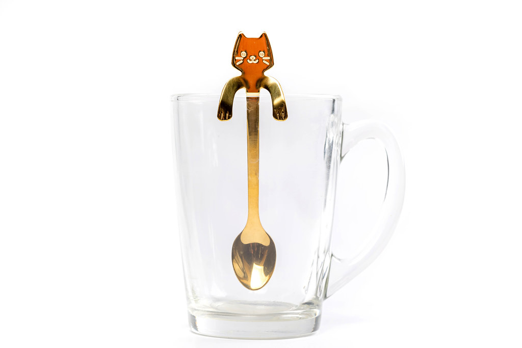 Cat-shaped teaspoon in an empty glass cup