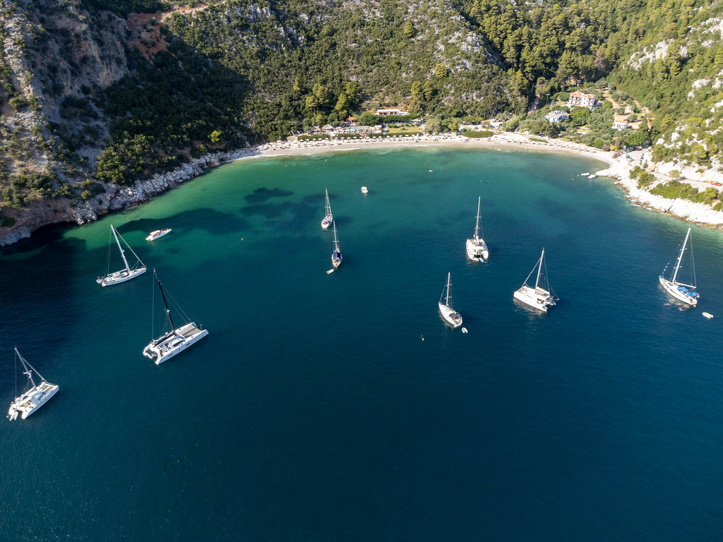 Catamarans and sailing boats in the emerald green bay of Limnonari with hills covered by pine trees