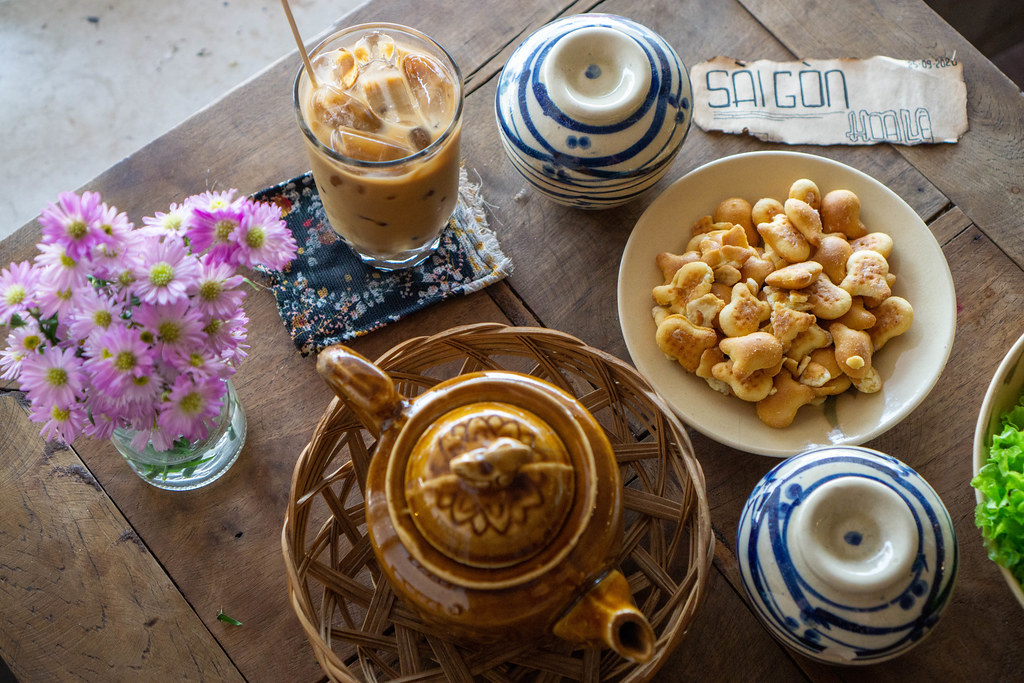 Ceramic Tea Pot with Vietnamese Iced Coffee, Cookies and Flowers on a Wooden Table in a Cafe in Saigon, Vietnam