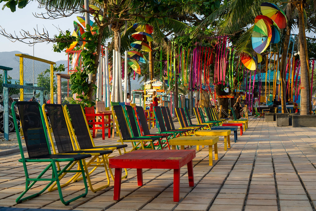 Chairs and Tables in different Colors at a popular Beach Bar with Palm Trees and Decorations at My Khe Beach in Da Nang, Vietnam