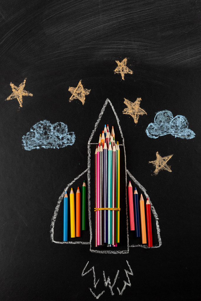 Chalk-drawn stars, clouds and airplane with colored pencils on dark background