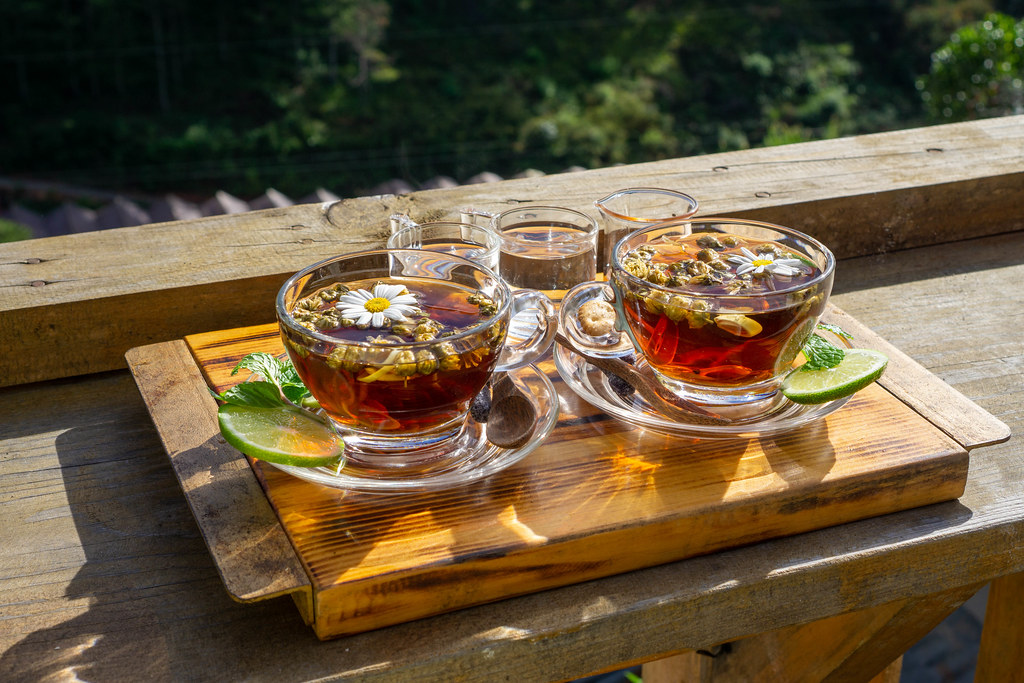 Chamomile Tea in Glass Cups on Glass Saucers with Daisy Flowers, Limes, Mint, Honey and Syrup on a Wooden Tray in a Cafe in Da Lat, Vietnam