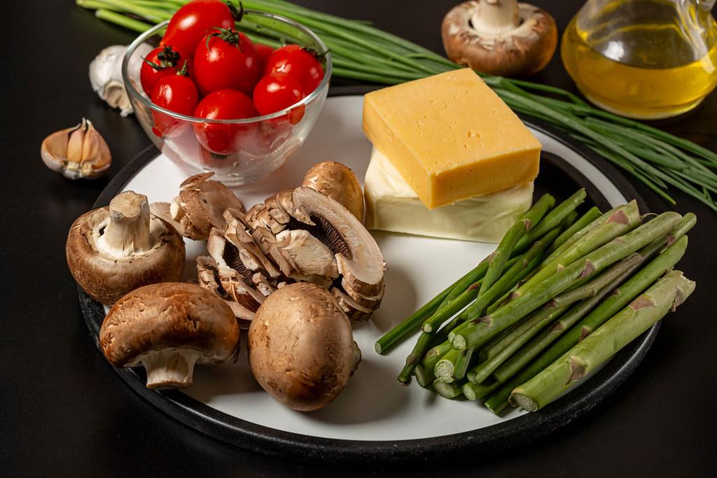 Champignons, tomatoes, asparagus, cheese and mozzarella, preparing pie filling