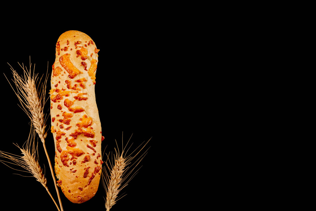 Cheese baguette on a black background with wheat spikelets, top view