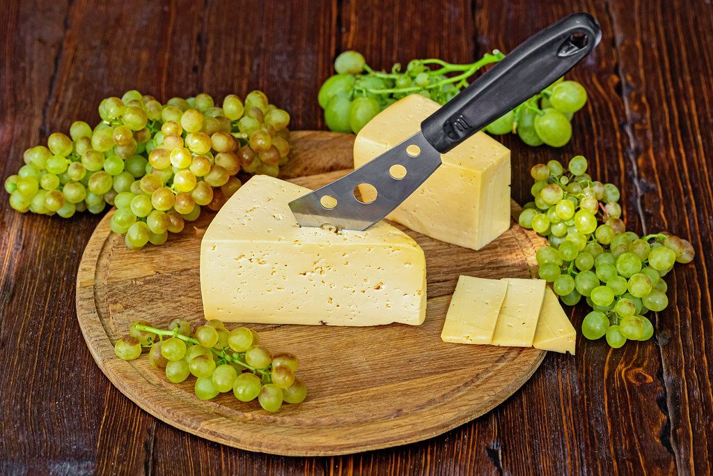 Cheese knife stuck in a piece of cheese on a round wooden board with ripe fresh grapes