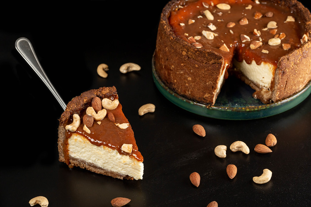 Cheesecake with condensed milk and nuts on a dark background