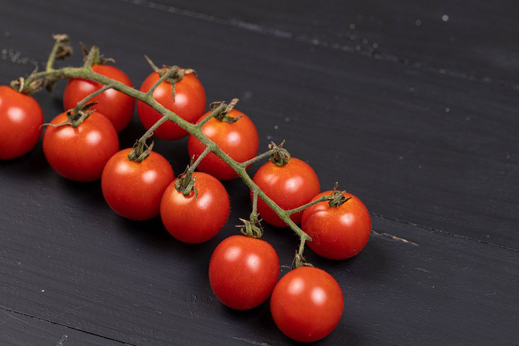 Cherry Tomatoes on the black wooden background