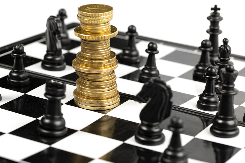 Chess game on chessboard, money and chess - concept strategy, investment and success