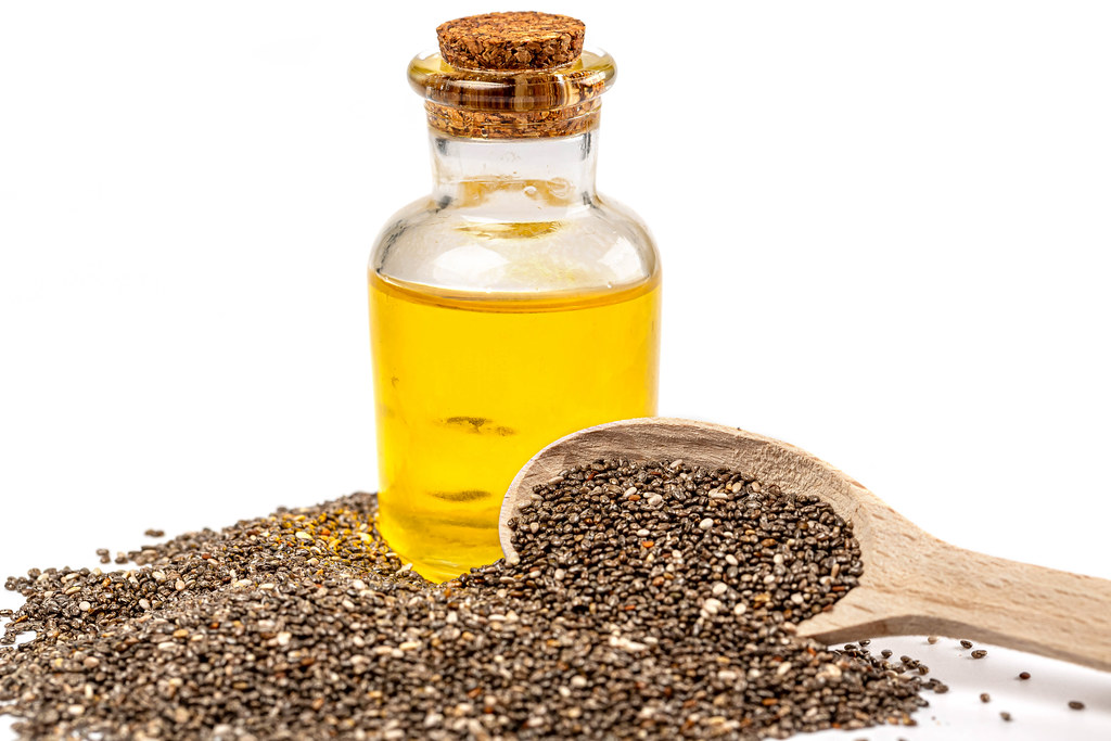 Chia seeds and chia oil on white background with wooden spoon