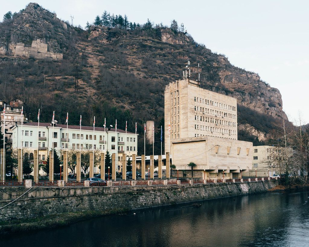 Chiatura cityhall: a prominent example of stalinist architecture overlooking a river with cliffs in the background