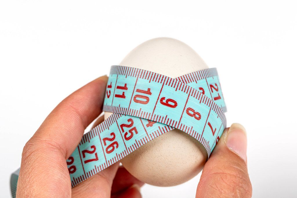 Chicken egg wrapped with measuring tape - diet food concept