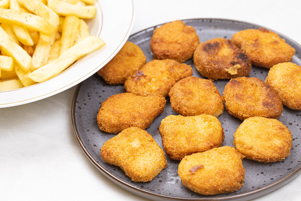 Chicken Nuggets served with french fries on the plate