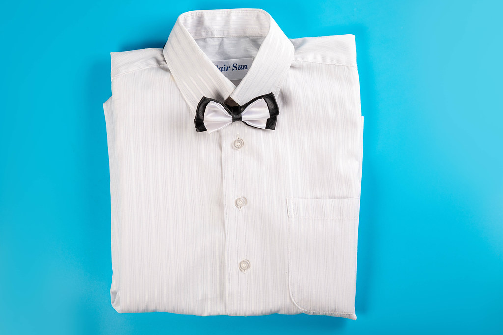 Children's white shirt with bow tie on blue, top view