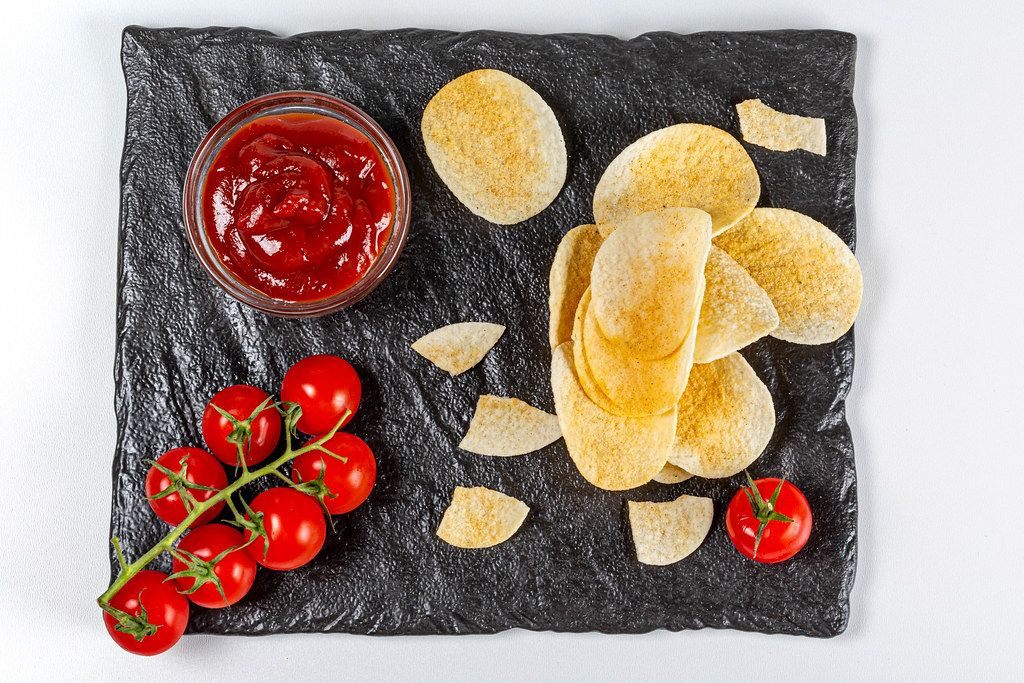 Chips and ketchup with tomato, top view