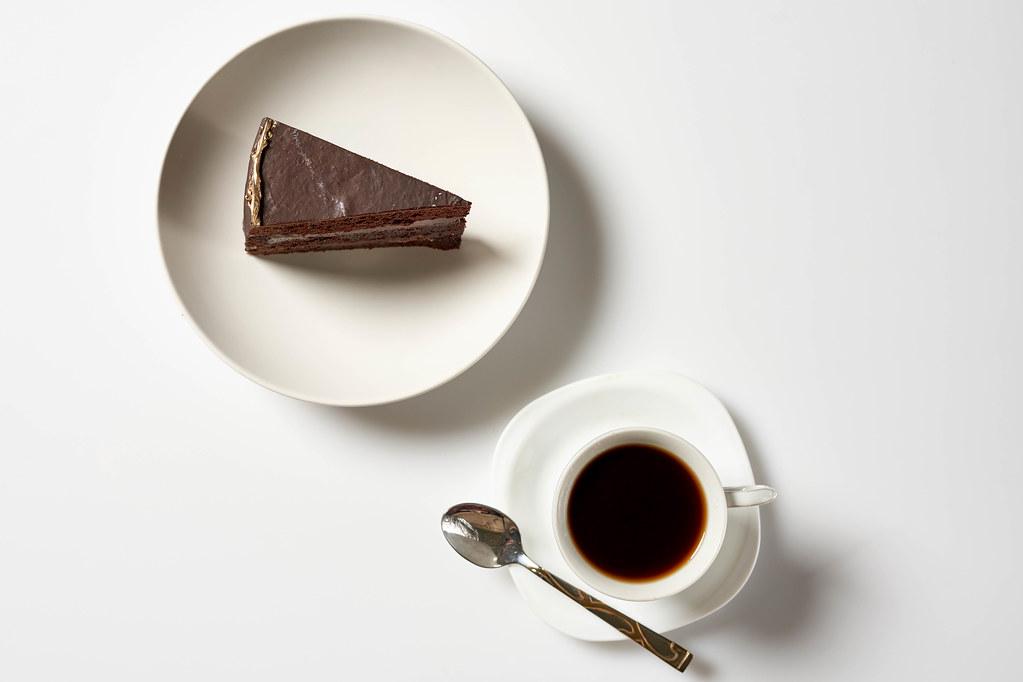 Chocolate cake slice with coffee mug on white background
