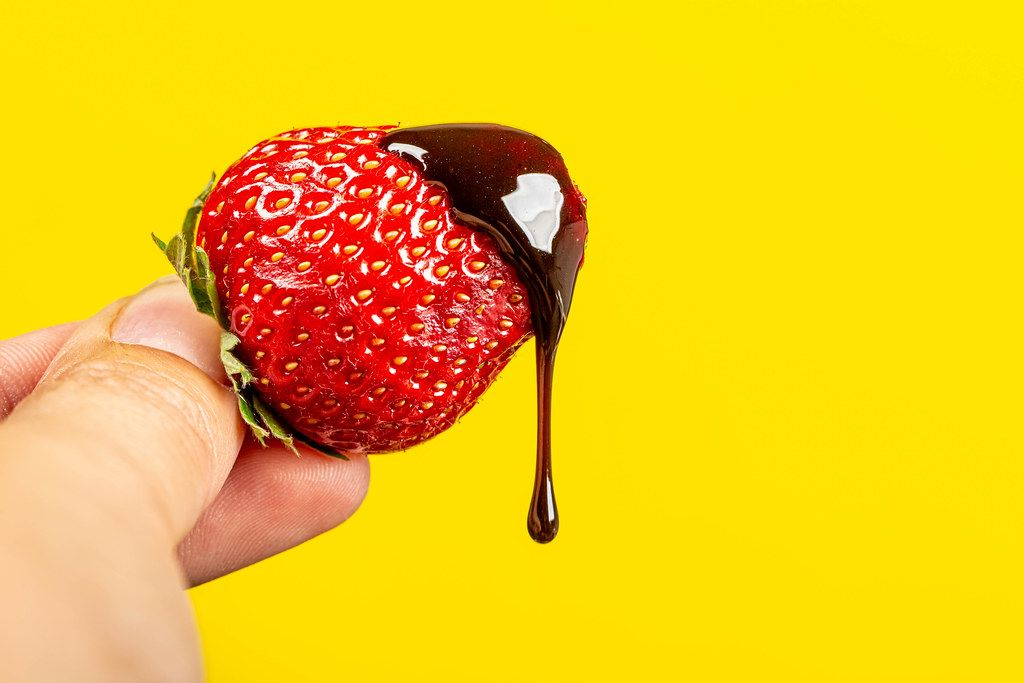 Chocolate drips from fresh strawberries on a yellow background
