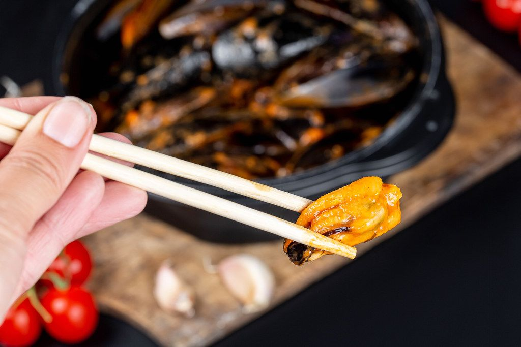 Chopsticks with mussels in a woman
