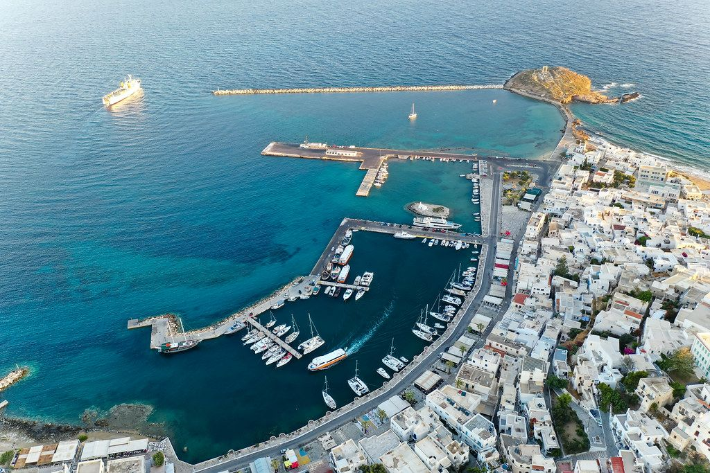 Chora, Naxos, with its port, a cargo ship leaving, and the Portara on the islet Palátia. Aerial shot of the city