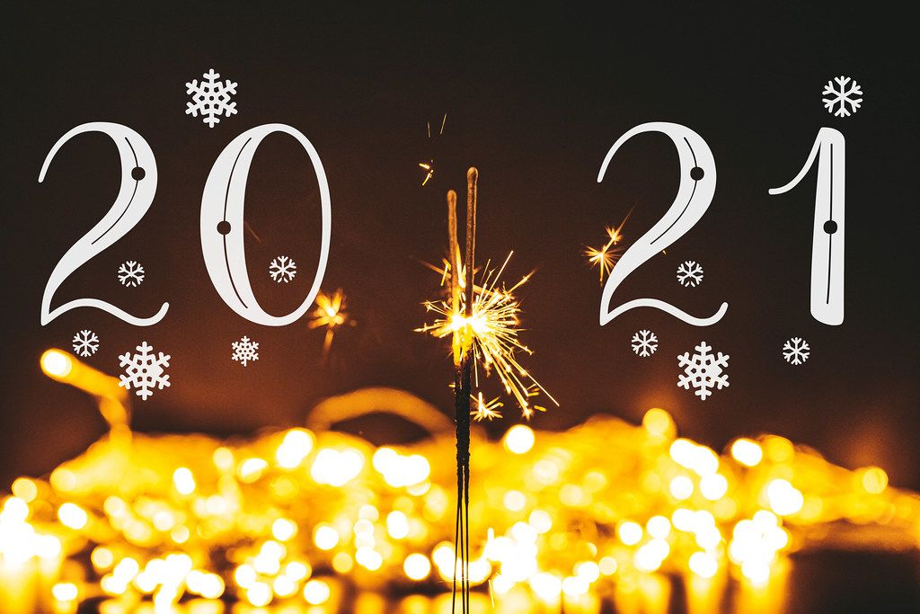 Christmas and new year background with glowing sparklers and golden bokeh
