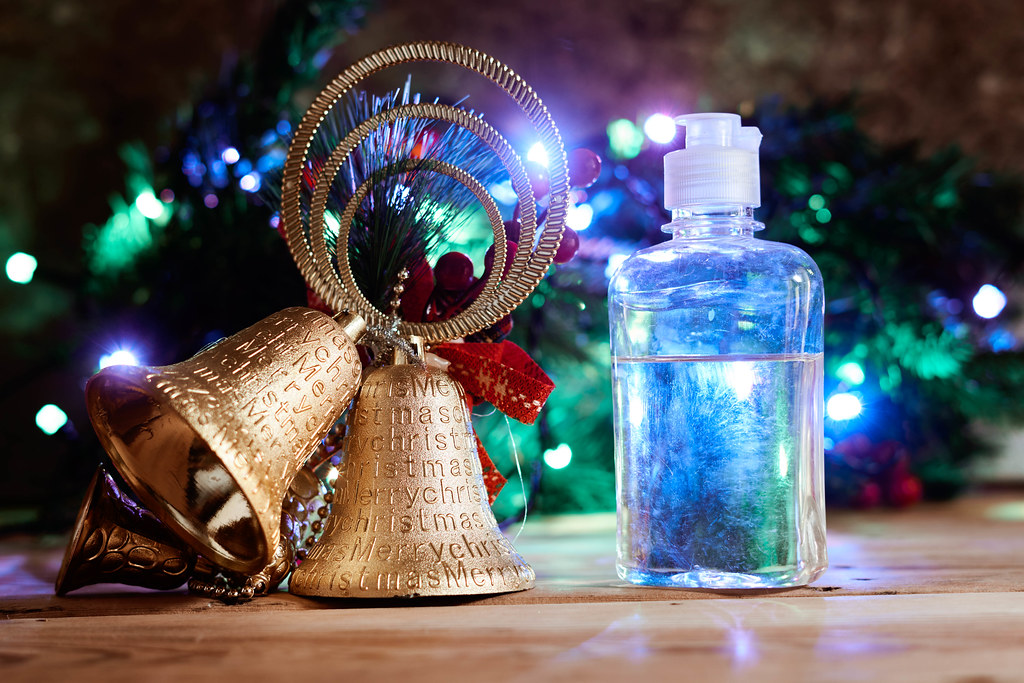 Christmas bell and bottle of antiseptic gel over decorated festive tree