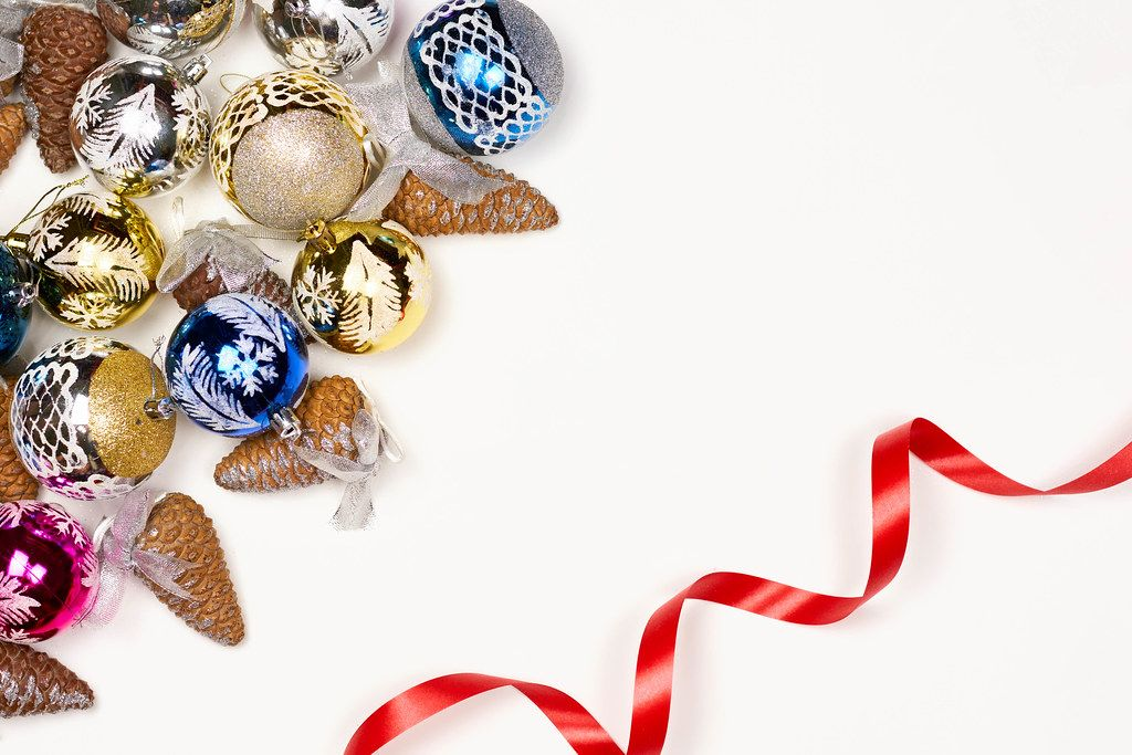 Christmas composition with Xmas gifts, toys, pine cones and ribbon on white background