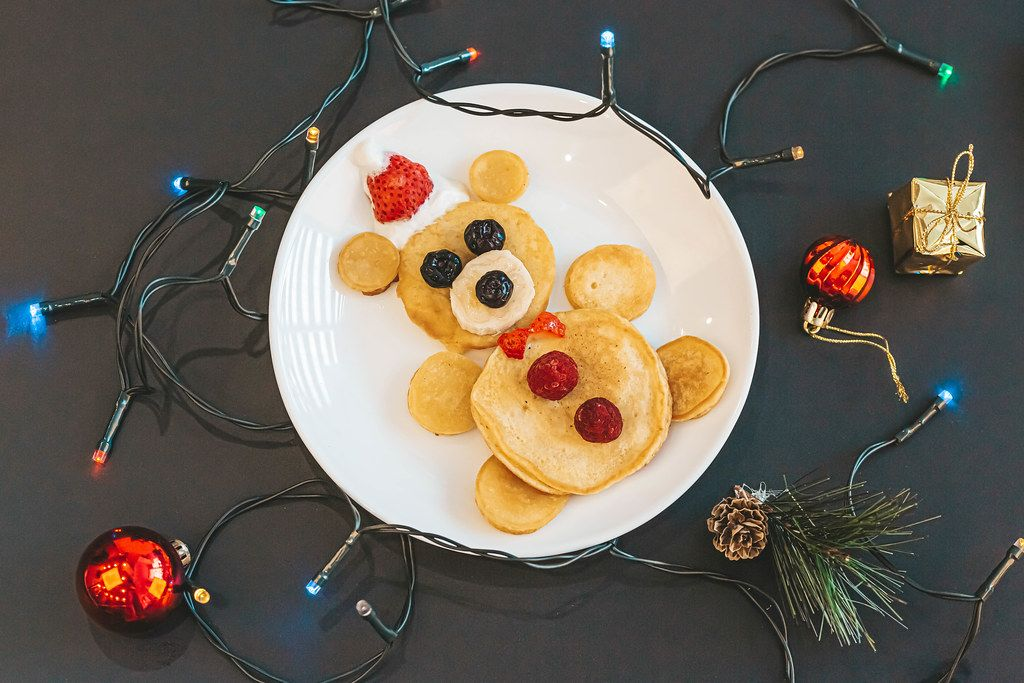 Christmas kids breakfast with bear pancakes and garland on dark background