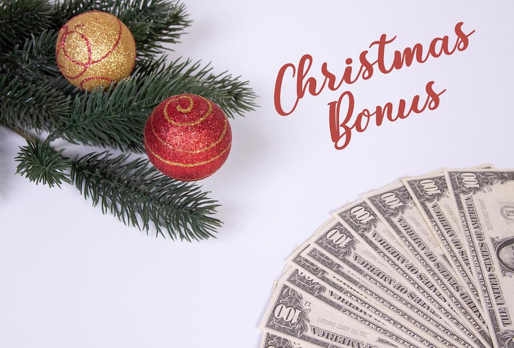 Christmas ornaments and dollar banknotes with Christmas Bonus text