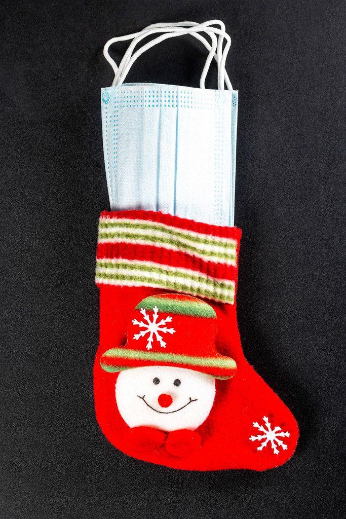Christmas sock with masks inside on black. Coronavirus concept and winter holidays