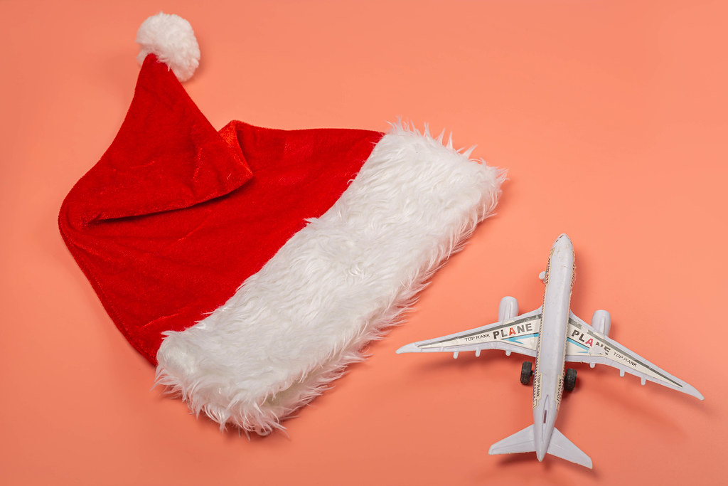 Christmas travel concept - santa hat and airplane on pink background