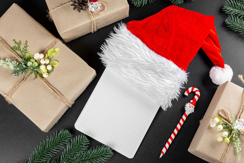 Christmas tree branches, wrapped gifts, santa hat, blank paper and a pen, top view