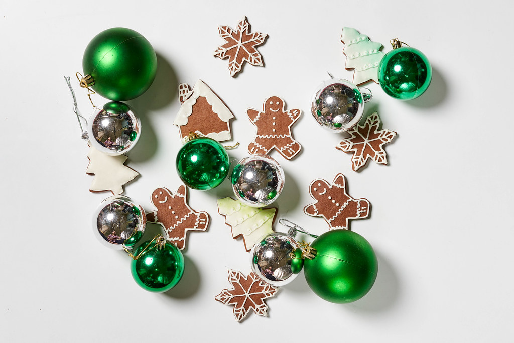 Christmas tree decorations and sweet cookies on white table