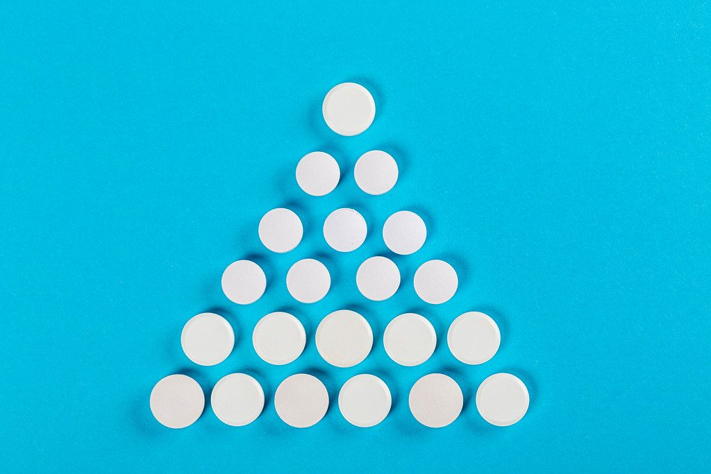 Christmas tree made of pills on a blue background