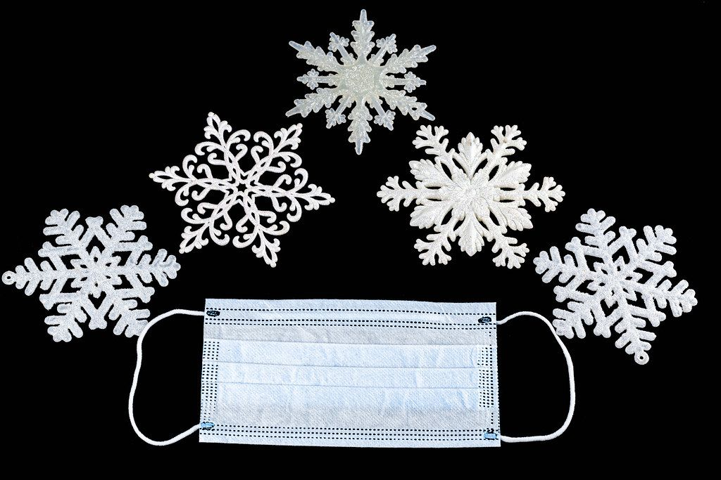 Christmas white snowflakes and medical mask on black background